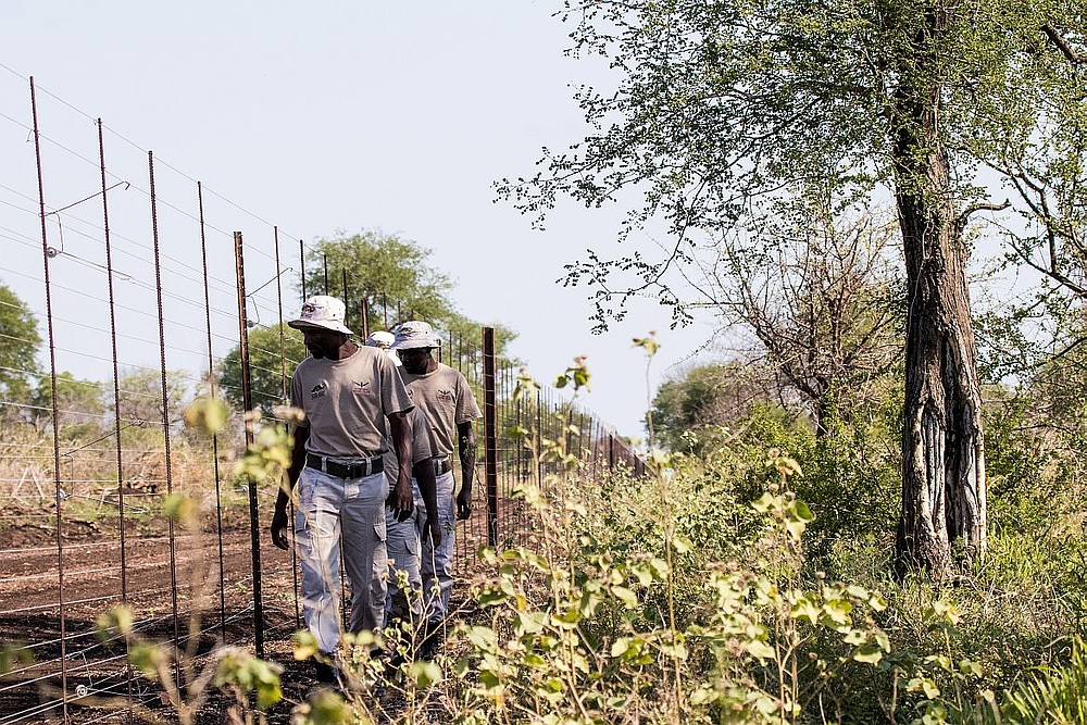 Village police in Mangalane patrol the fence.