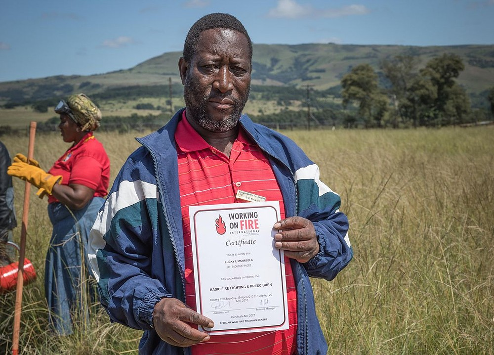 Man holds up training certificate.