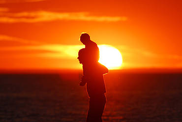 A father and his child enjoying the sunset over Lake Ontario, Ontario, Canada